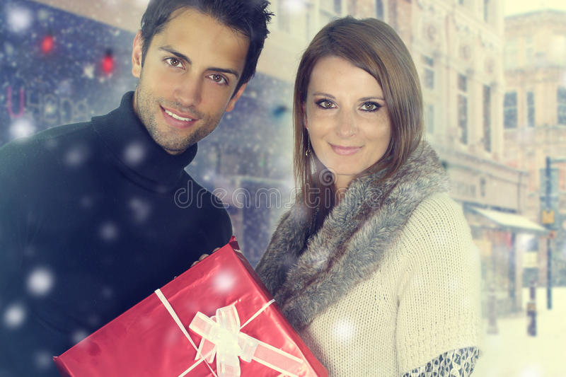 Young couple holding a Christmas present. Outdoors stock photo