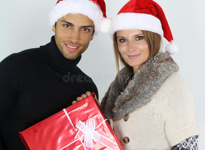 Young couple holding a Christmas present. Over a white background royalty free stock photo