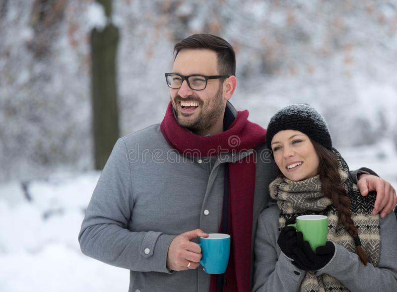 Man and woman with hot drink on snow. Young couple holding cup of hot drink on snow in forest stock image