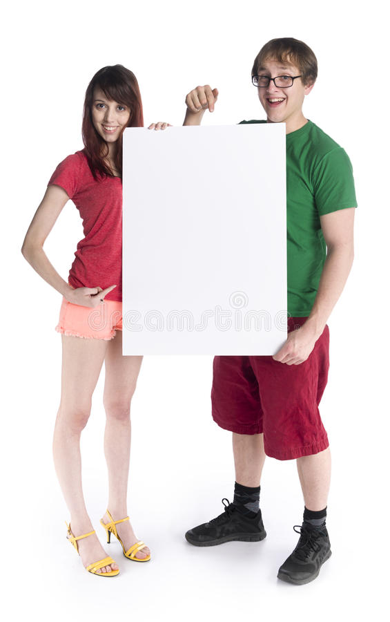 Young Couple Holding Empty White Cardboard. Full Length Shot of a Young Couple Holding Empty White Cardboard, Emphasizing Copy Space, While Smiling at the Camera stock photo