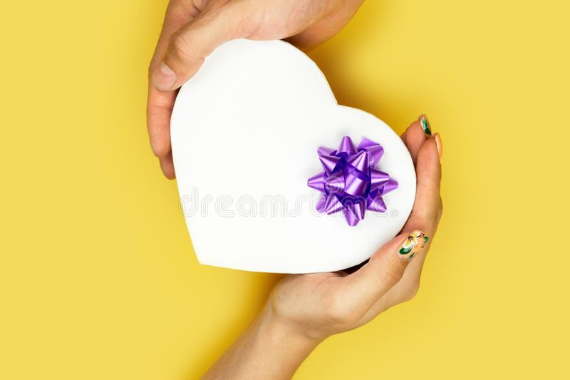 New Year, Christmas Concept. A young couple holding a gift box in the shape of a heart. Valentine gift. of the stock photo