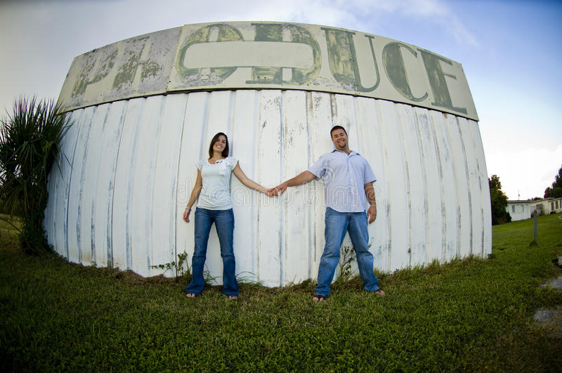 Young couple holding hands. A young couple holding hands in front of country produce sign royalty free stock photo