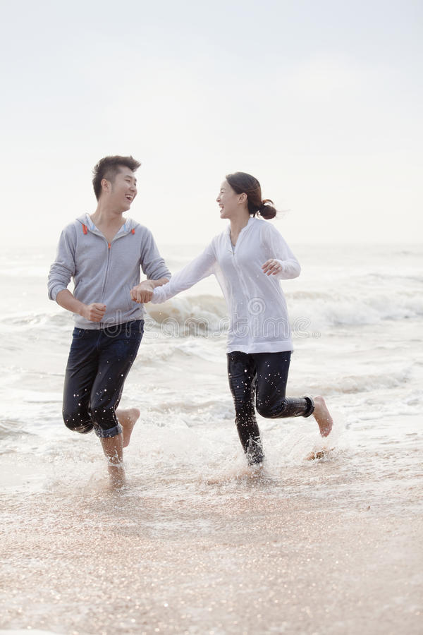 Free Young Couple Holding Hands And Running By The Waters Edge On The Beach, China Stock Photos - 31129773