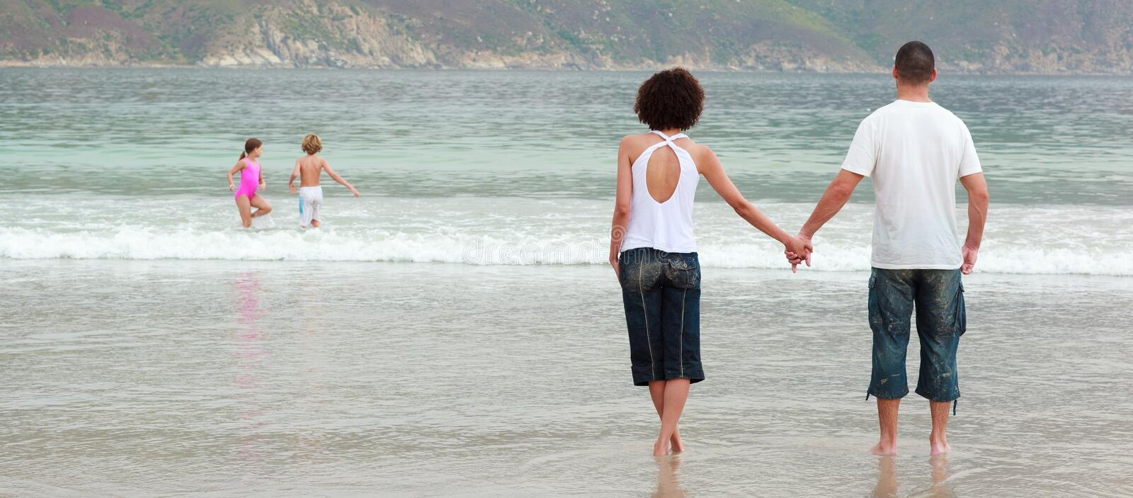 Young couple holding hands on the beach stock photos