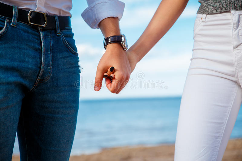 Young couple holding hands at the beach royalty free stock images
