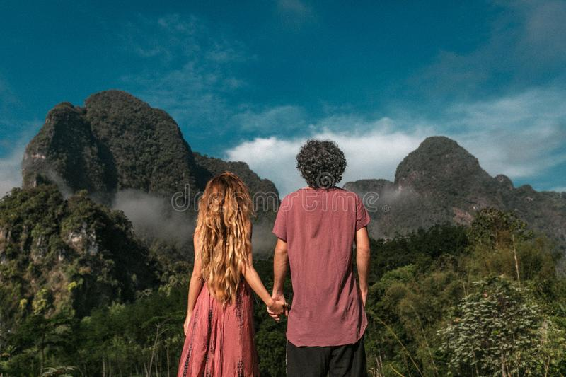 Young couple holding hands enjoying mountain view royalty free stock photos