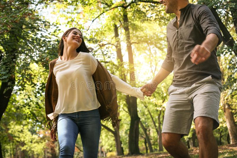 Young couple holding hands and running together trough park. royalty free stock photography