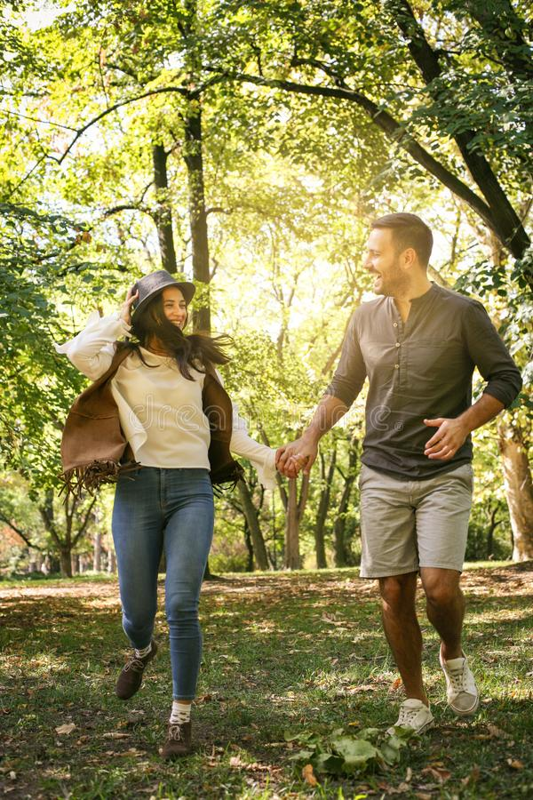 Young couple holding hands and running together trough park. stock photos