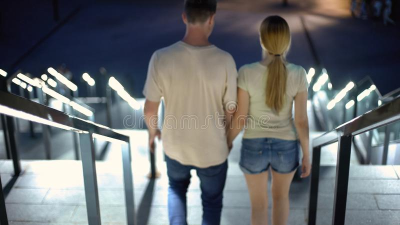 Young couple holding hands, walking downstairs in night city, togetherness royalty free stock photo