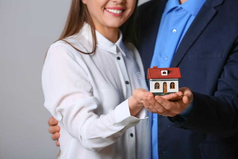 Young couple holding house model on grey background. Closeup. Home insurance stock photos