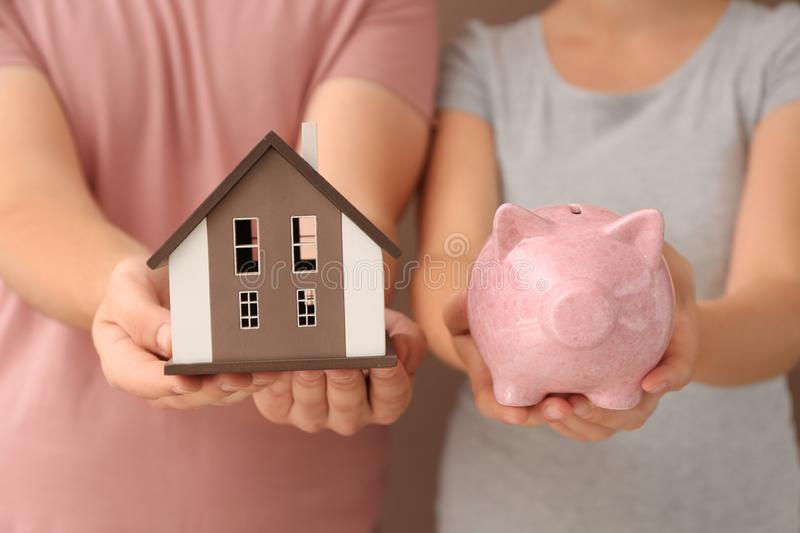 Young couple holding house model and piggy bank, closeup. Mortgage concept stock photo
