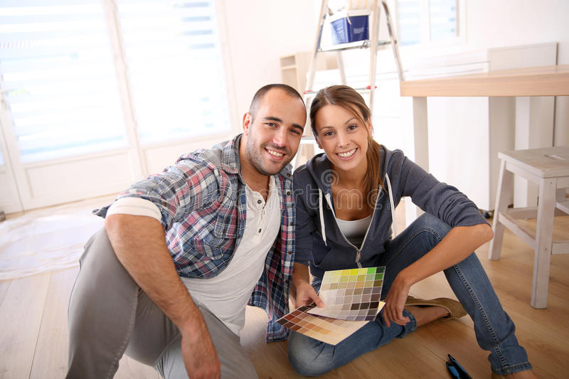 Young couple at home choosing decorating colours stock photography