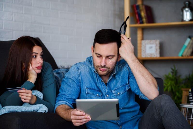 Young couple at home having financial difficulties. Young Couple Shopping Online At Home. Young couple at home having financial difficulties stock photos