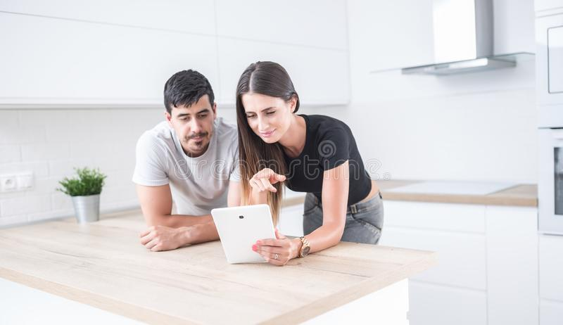Young couple in home kitchen using tablet stock photography