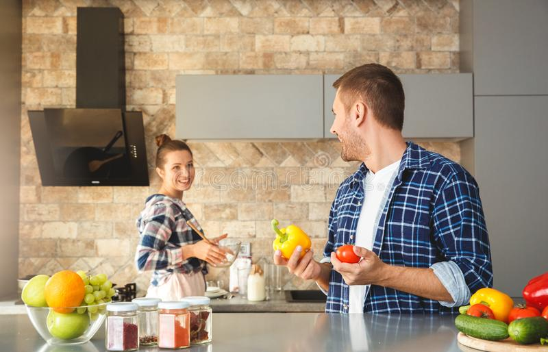 Young couple at home standing in kitchen together man holding vegetables lookign back at woman cooking cheerful stock images