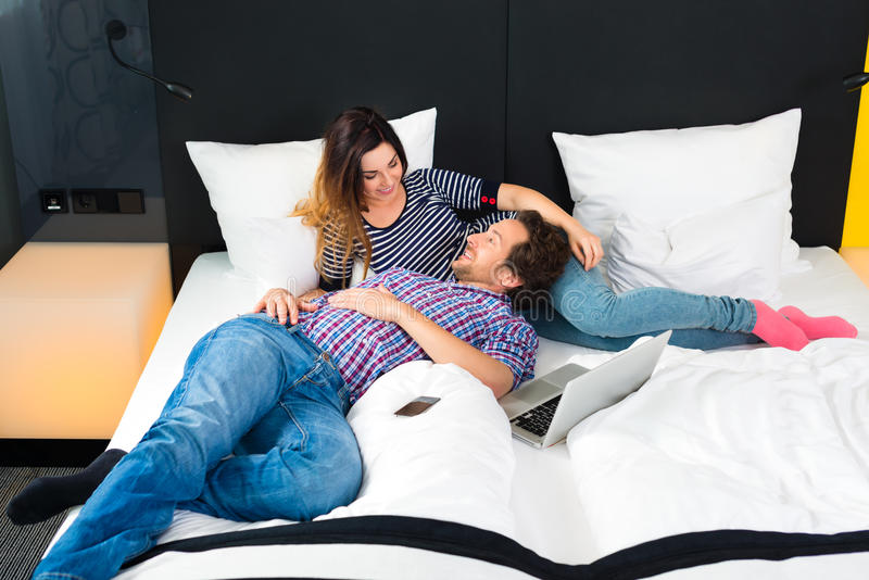Young couple in Hotel in bed with wifi and computer stock image