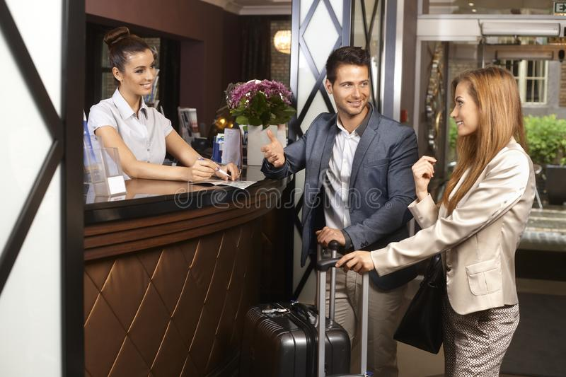Young couple at hotel reception stock photography