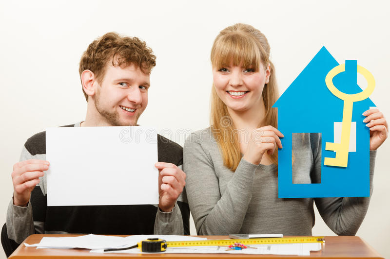 Young couple with house and paper. Real estate ownership finance concept. Young couple with house and paper sheet copy space for text. Man and women preparing stock photo