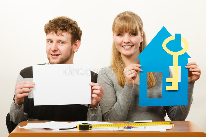 Young couple with house and paper. Real estate ownership finance concept. Young couple with house and paper sheet copy space for text. Man and women preparing royalty free stock photos