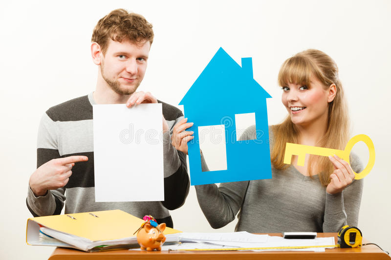 Young couple with house and paper. Real estate ownership finance concept. Young couple with house and paper sheet copy space for text. Man and women preparing royalty free stock photo