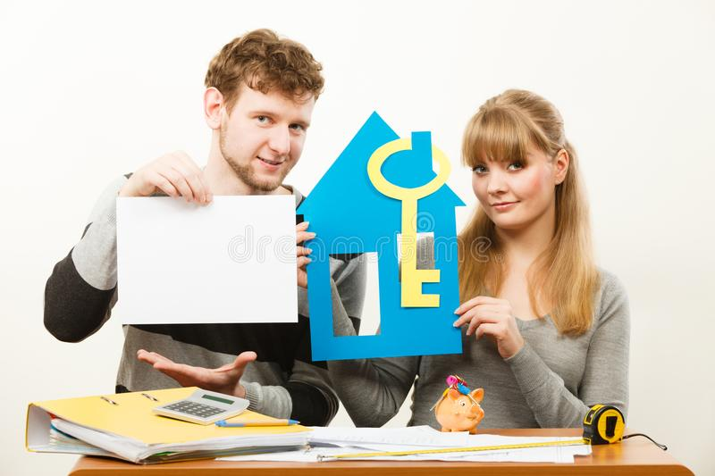 Young couple with house and paper. Real estate ownership finance concept. Young couple with house and paper sheet copy space for text. Man and women preparing stock photos