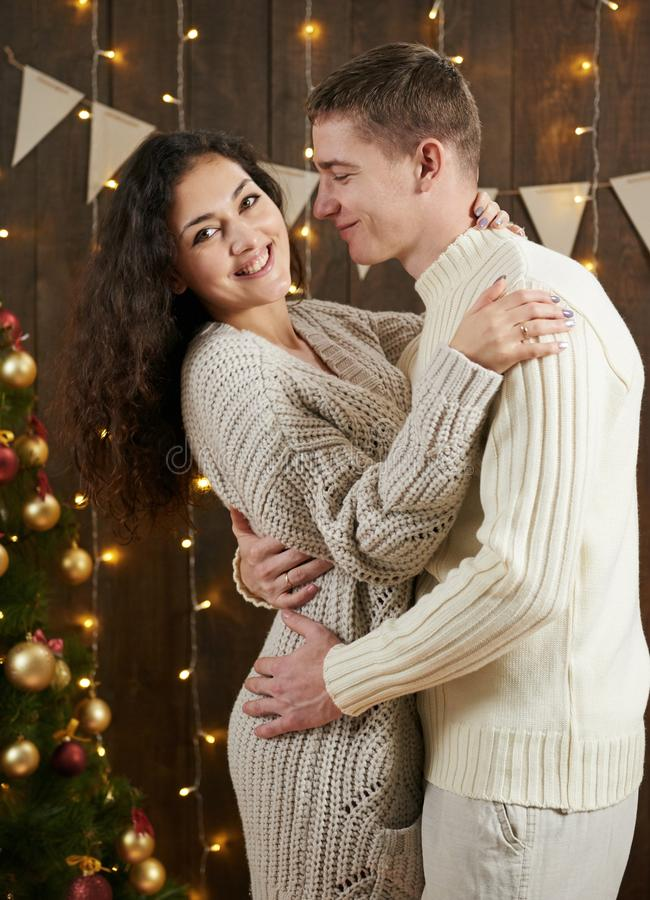 Young couple hugging in dark wooden interior with lights. Romantic evening and love concept. New year holiday. Christmas lights an. D decoration. Dressed in royalty free stock images