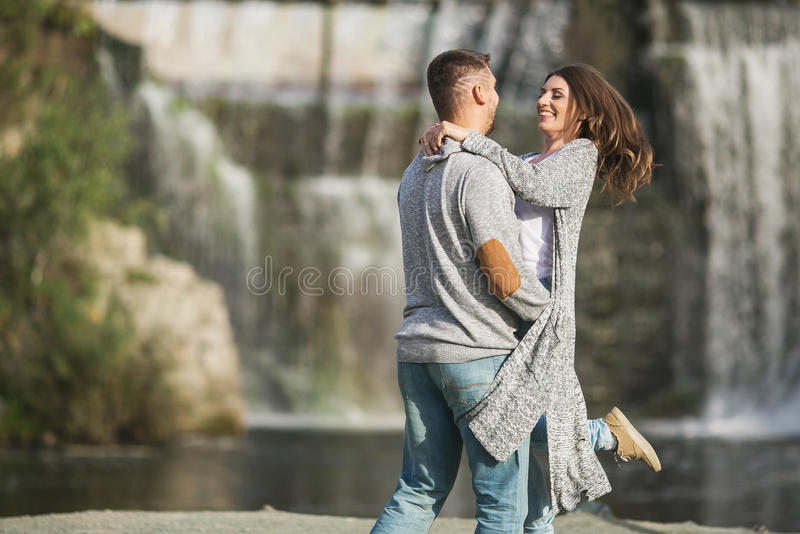 A young couple is hugging each other near a waterfall royalty free stock image