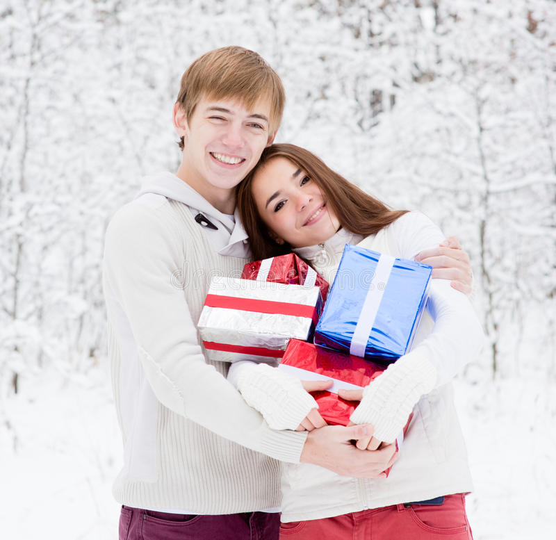 Young couple hugging and holding gifts stock photography