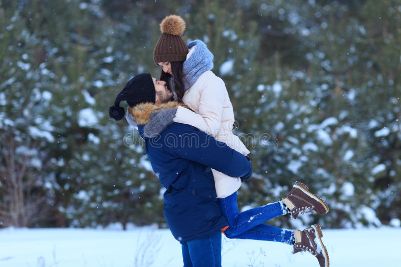 Young couple hugging and kissing in winter forest royalty free stock image