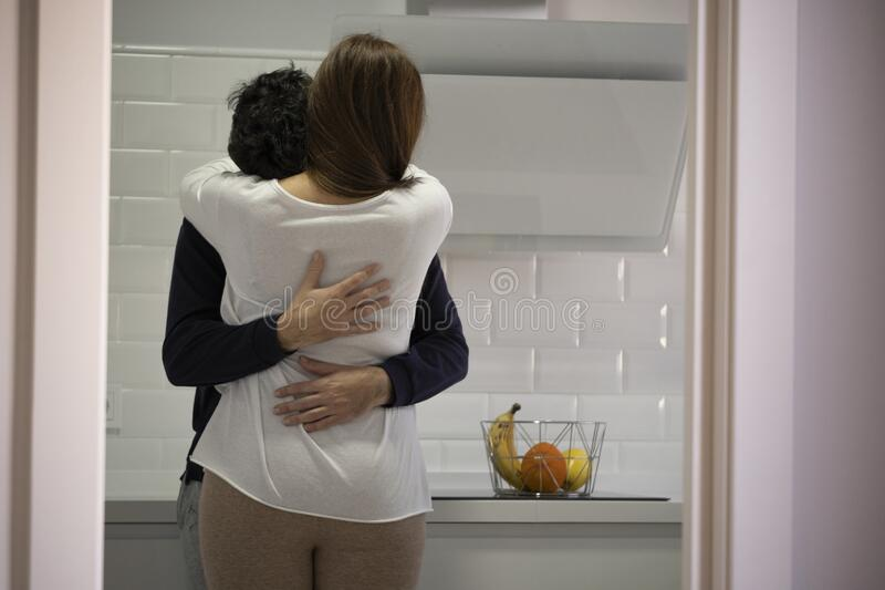 Young couple hugging in the kitchen of their house. concept of psychological help royalty free stock images