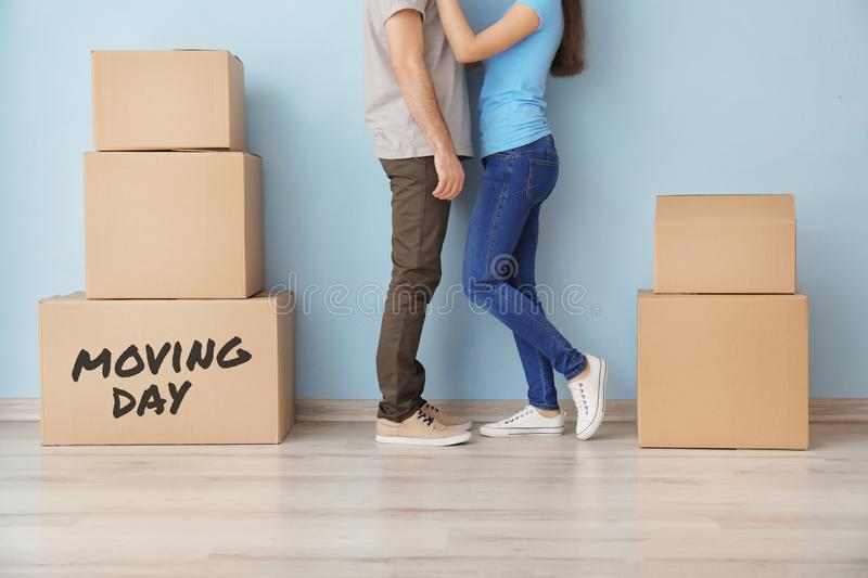 Young couple hugging near boxes indoors. Moving into new house royalty free stock images