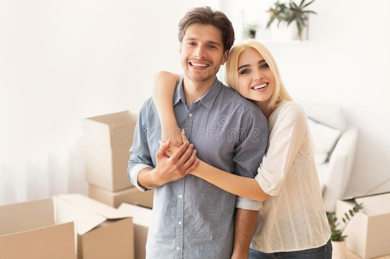 Young Couple Hugging Posing Among Moving Boxes In New Home stock photos