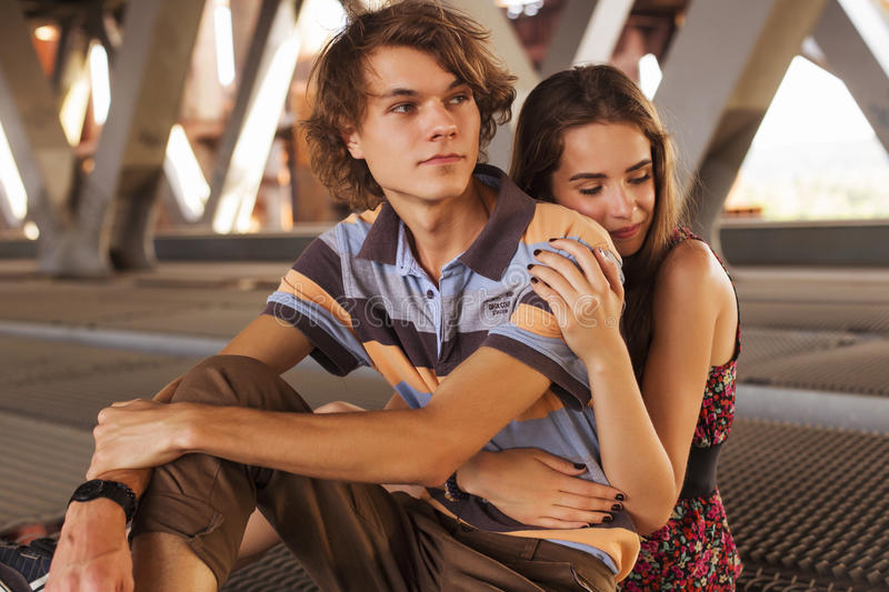 Young couple hugging in the summer daylight on a bridge construction in the city outdoors. copy space royalty free stock photos