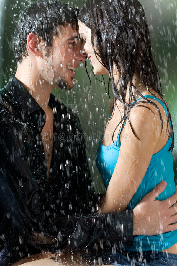 Young couple hugging under a rain stock images
