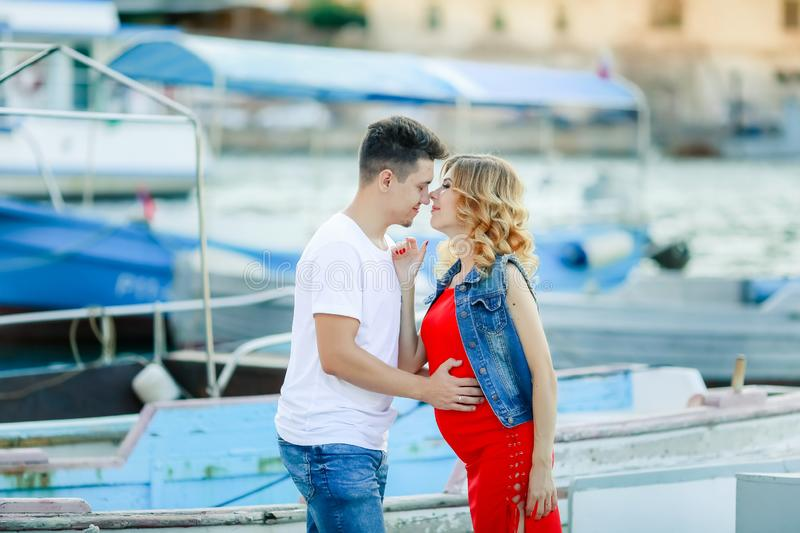 Young couple hugs and relaxing at dock near boat, on sunny summer day. Woman and man in fashionable clothes stands near. Young couple hugs and relaxing at dock royalty free stock image