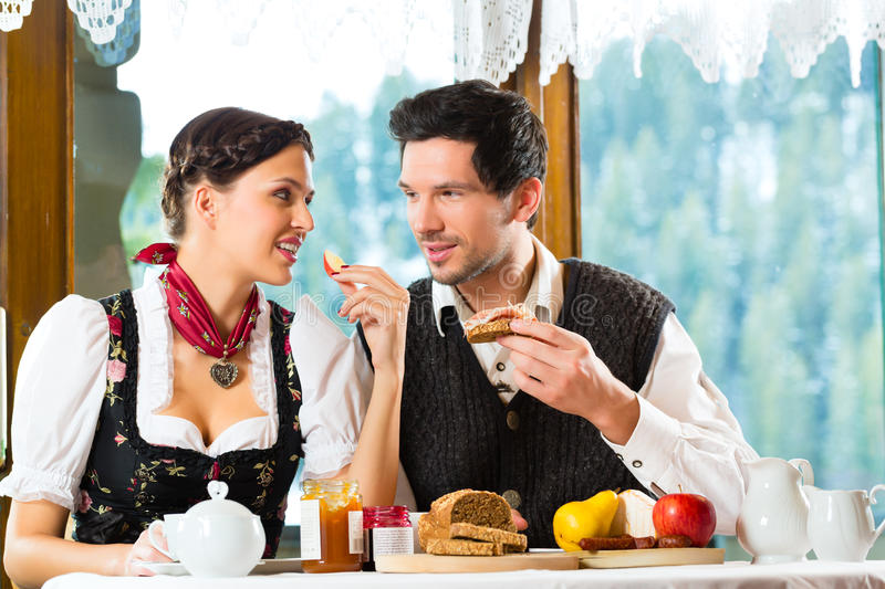 Young couple in a hunter's cabin eating stock images