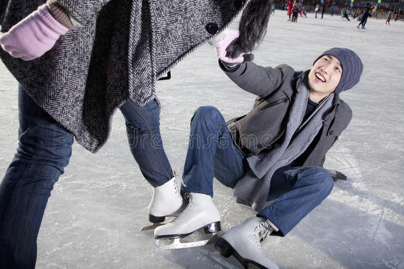 Young couple at ice rink, woman helping man up after falling stock image