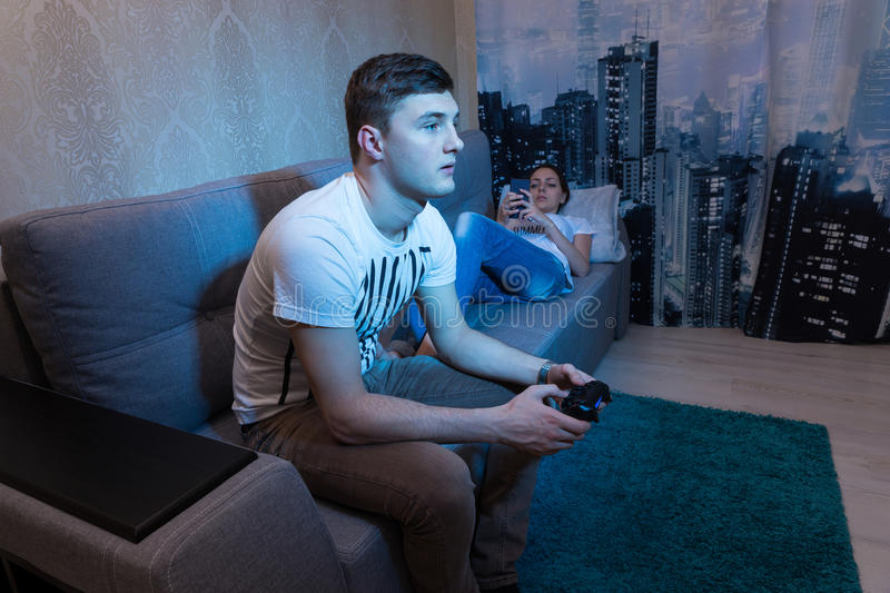 Young couple ignoring each other at home. Where young men playing a video game holding a console while his girlfriend lying on the sofa and surf the Internet stock photo