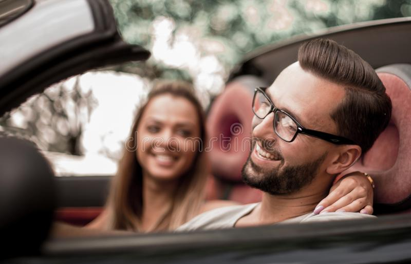 Young couple inside a convertible car for a day trip. royalty free stock image