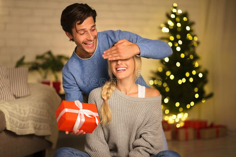 Young couple interchanging gifts on Christmas eve stock image