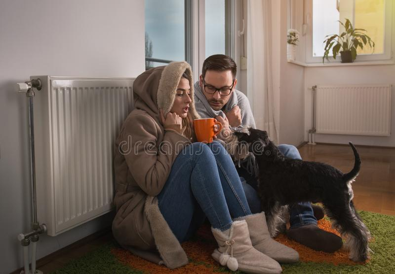 Couple with dog sitting beside radiator and freezing. Young couple in jacket and covered with blanket sitting on floor beside radiator with dog and trying to stock images