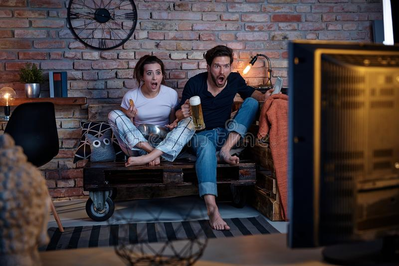 Young couple jittering front of tv stock image