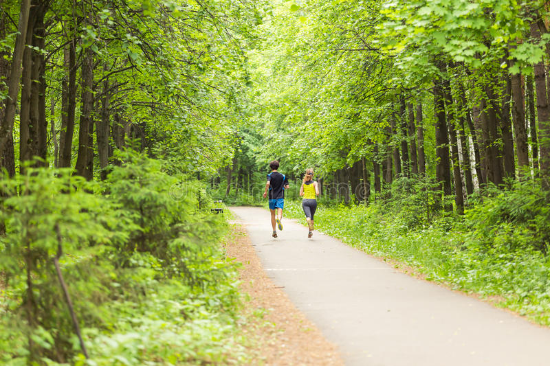 Young couple jogging in park at morning. Health and fitness concept royalty free stock images