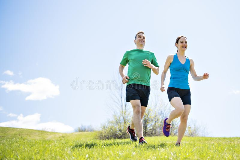 Young couple jogging in park at morning. Health and fitness. royalty free stock photos