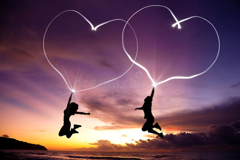 Young couple jumping and drawing connected hearts. By flashlight in the air on the beach before sunrise stock images