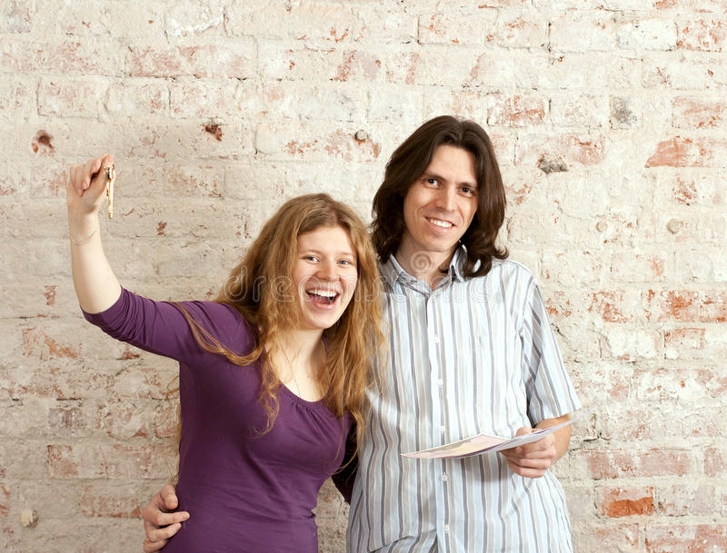The young couple with keys and property deed. In unrepair appartment stock image