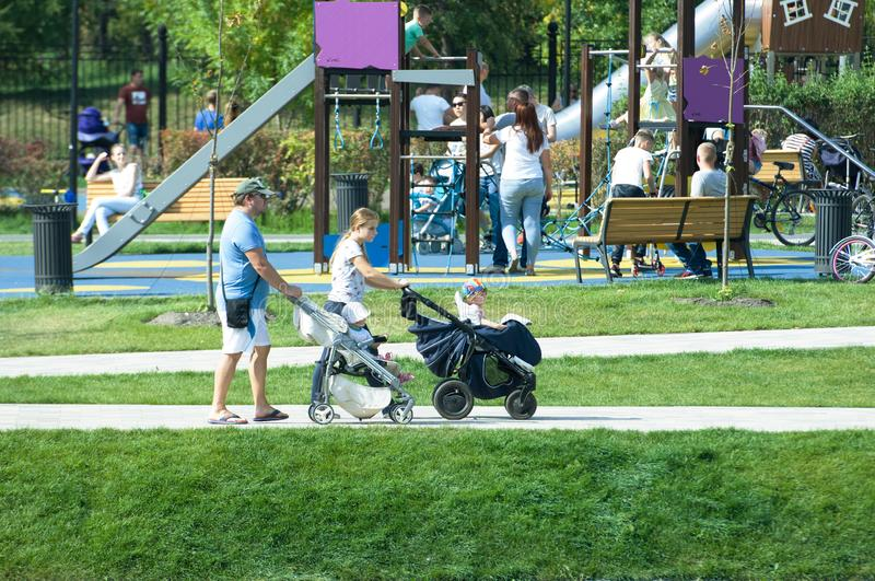 Young couple with kids stroller walking in Butovo park, Moscow, Russia stock photography