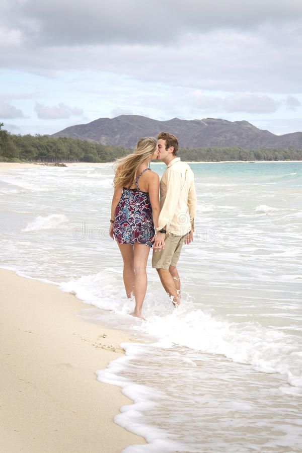 A Young Couple Kiss In The Waves Stock Photos