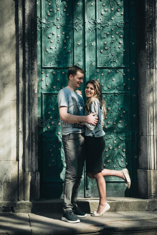 Young couple kisses near the vintage green door. royalty free stock photography