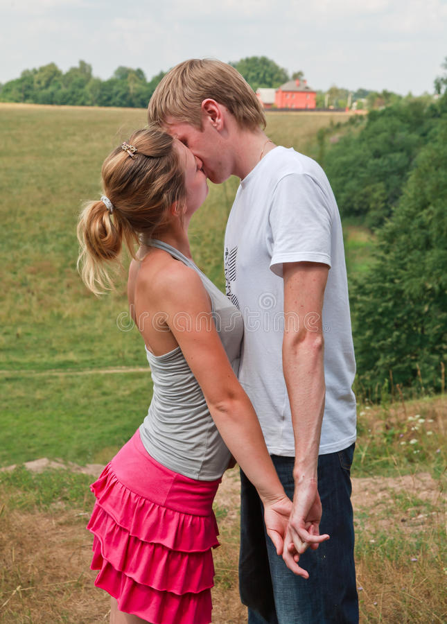 Young couple kissing. Young couple in love kissing each other, countryside background stock photos